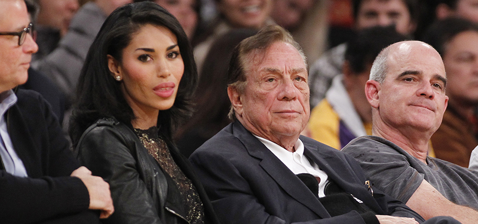 """Los Angeles Clippers owner Donald Sterling, center, and V. Stiviano, left, watch the Clippers play the Los Angeles Lakers during an NBA preseason basketball game in Los Angeles on Monday, Dec. 19, 2010. The NBA is investigating a report of an audio recording in which a man purported to be Sterling makes racist remarks while speaking to Stiviano. NBA spokesman Mike Bass said in a statement Saturday, April 26, 2014, that the league is in the process of authenticating the validity of the recording posted on TMZ's website. Bass called the comments """"disturbing and offensive."""" (AP Photo/Danny Moloshok)"""