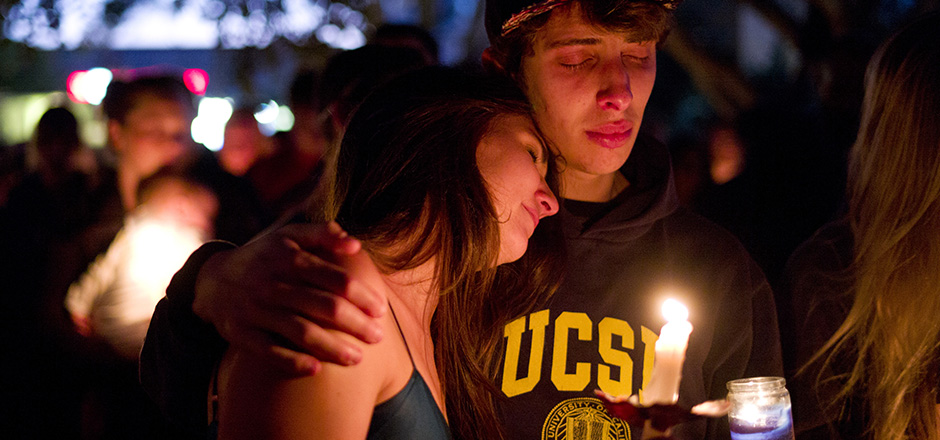 Two students comfort each other during a candlelight vigil held to honor the victims of Friday night's mass shooting on Saturday, May 24, 2014, in Isla Vista, Calif. Sheriff's officials said Elliot Rodger, 22, went on a rampage near the University of California, Santa Barbara, stabbing three people to death at his apartment before shooting and killing three more in a crime spree through a nearby neighborhood. (AP Photo/Jae C. Hong)