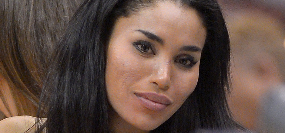 In this photo taken on Friday, Oct. 25, 2013, V. Stiviano, left, watches the Clippers play the Sacramento Kings during the first half of an NBA basketball game in Los Angeles. The NBA is investigating a report of an audio recording in which a man purported to be Sterling makes racist remarks while speaking to Stiviano. (AP Photo/Mark J. Terrill)